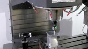 Probe inspecting rectangular part in CNC machine.