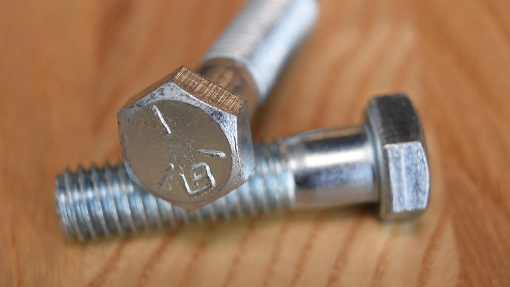 Two zinc-plated hex head screws, often called bolts.