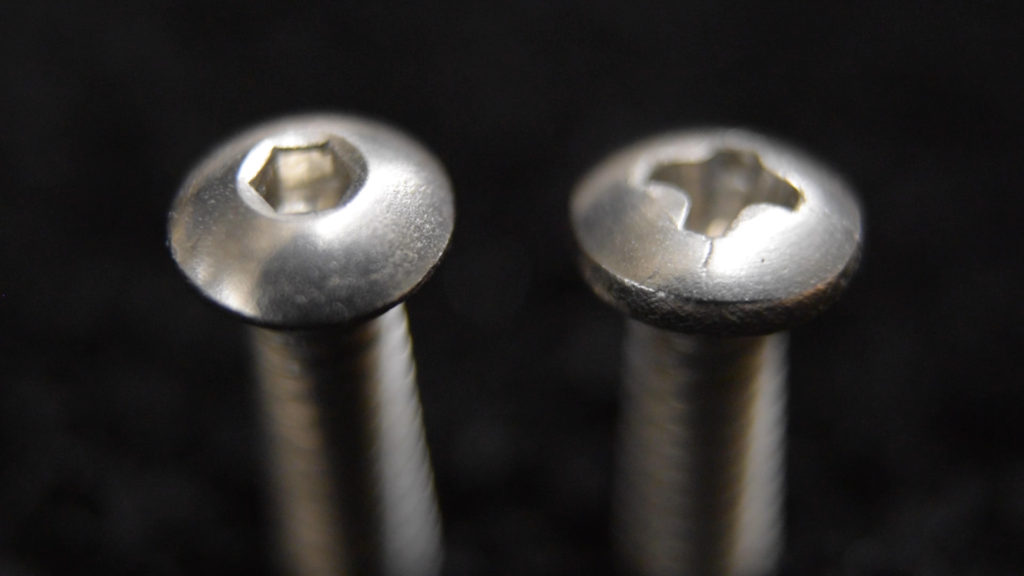 A comparison of two round head screws with zinc plating.