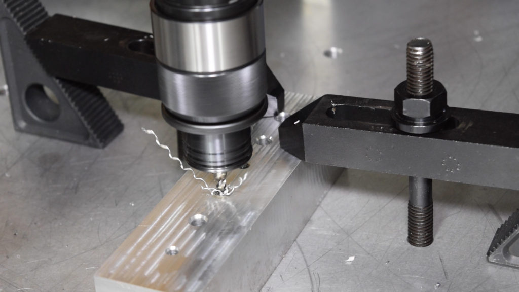 A powered tapping head cutting threads into an aluminum workpiece